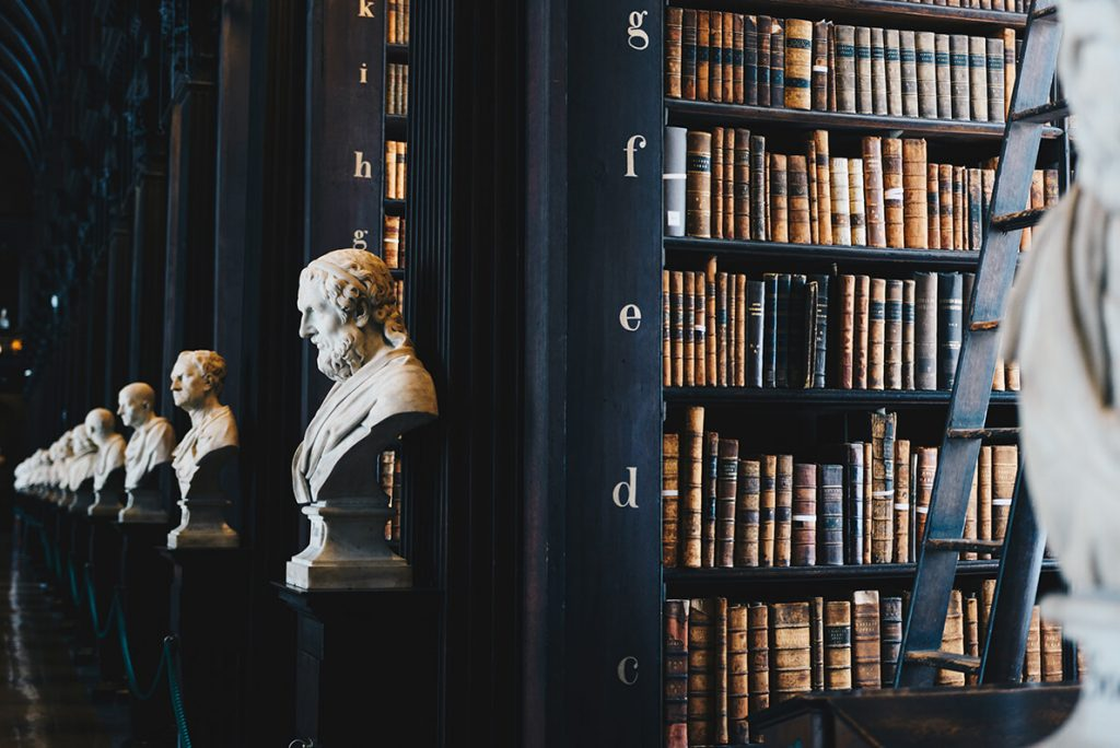 Leather-bound books in a dark library.